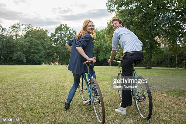 Smiling young couple with bicycles in park