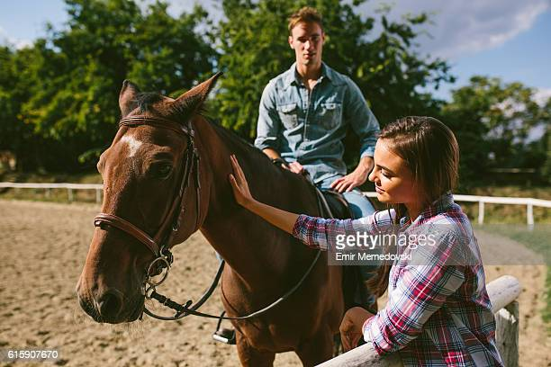 Smiling young couple with horse outdoors.