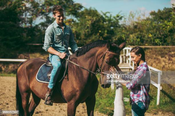 Smiling young couple with horse outdoors