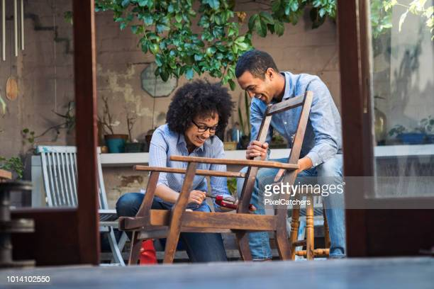 smiling young couple working together to restore a chair - diy stock pictures, royalty-free photos & images