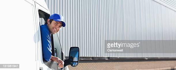 Lächelnder, junger Lastauto Fahrer Spähen aus dem Fenster