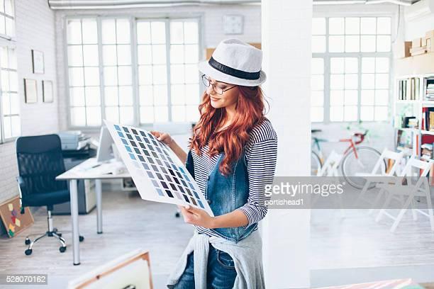 Lächelnde junge designer schaut an Farbprobe im Büro