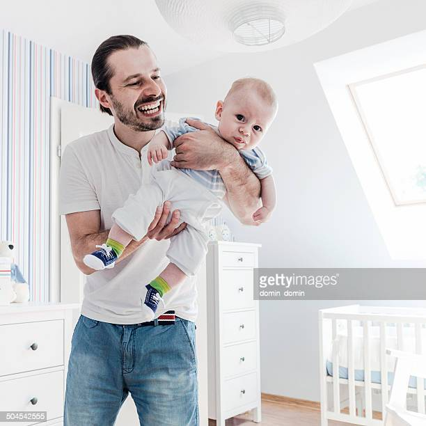 Smiling young father holding unhappy baby boy, hardships of fatherhood