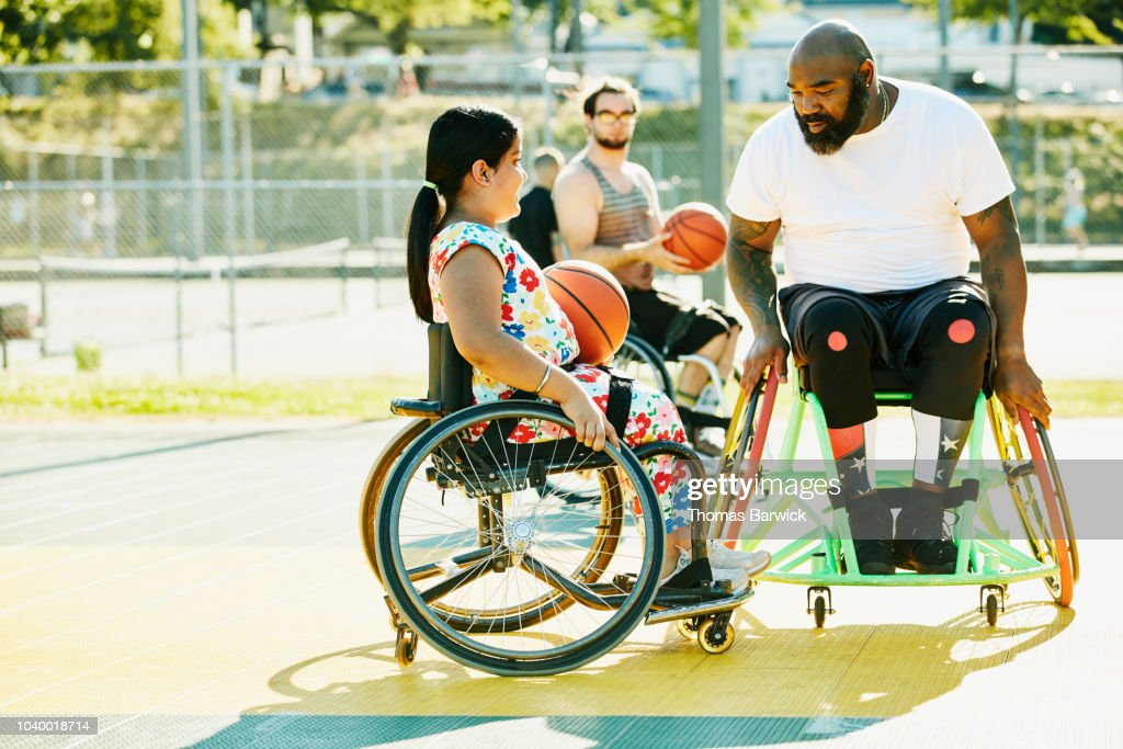 Smiling young female adaptive athlete getting advice from adaptive basketball coach during practice on summer evening : Stock Photo