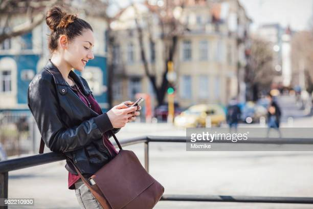 smiling young female browsing on her phone while waiting on the street - crossbody bag stock pictures, royalty-free photos & images