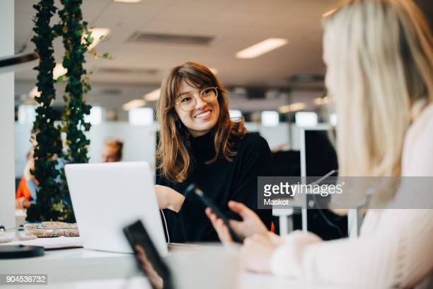 smiling young female colleague sitting at desk in office - smart casual stock pictures, royalty-free photos & images