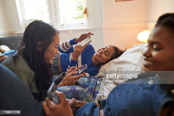 smiling young female friends using phones at home - woman texting stockfoto's en -beelden