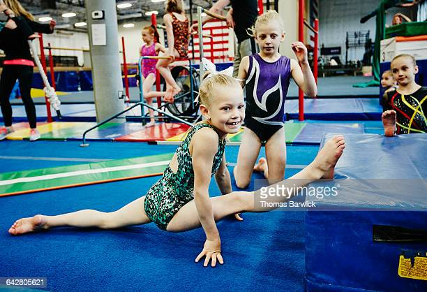 smiling young female gymnast stretching - girl with legs spread stock photos and pictures