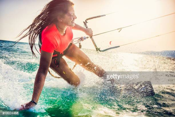 smiling young female kiteboarder on the sea - vitality stock pictures, royalty-free photos & images