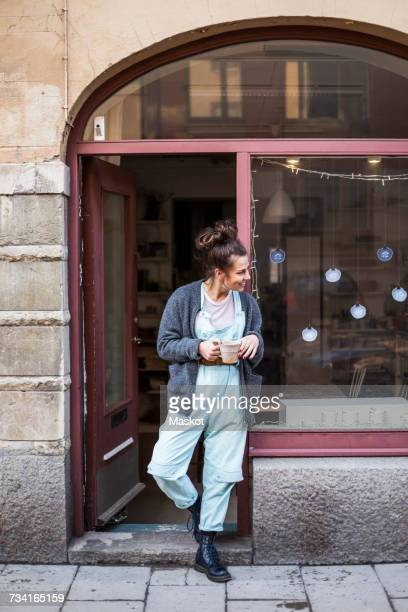 Smiling young female potter standing with coffee cup at doorway of ceramics store