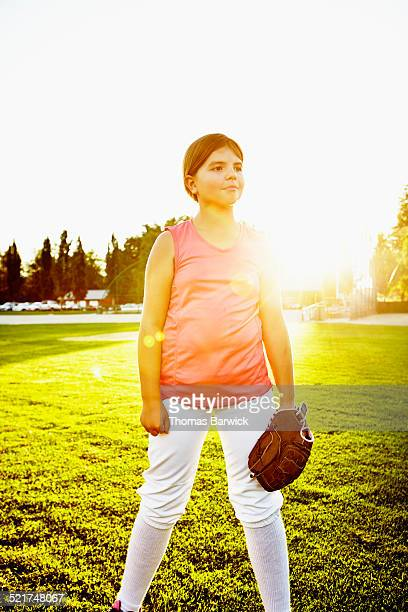 Smiling young female softball player on field