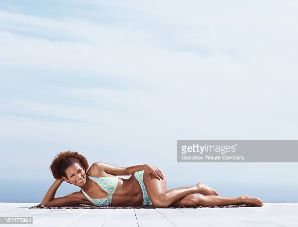 Smiling young female sunbathing while lying on a porch