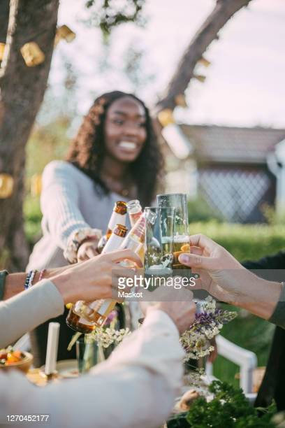 smiling young female toasting beer with friends in backyard - honour stock pictures, royalty-free photos & images