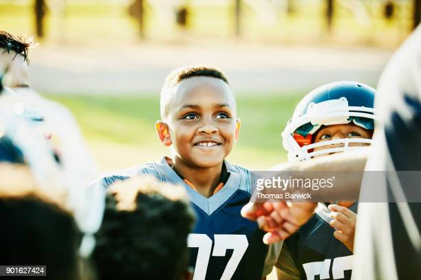 Smiling young football player listening to coach with teammates after game
