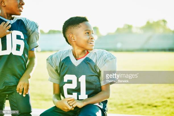 Smiling young football player sitting on bench with teammates before football game