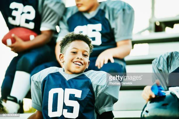 Smiling young football player sitting on bleachers with teammates after practice