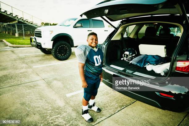 Smiling young football player standing by tailgate of car after football game