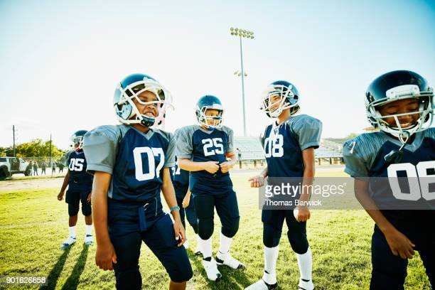 Smiling young football player standing on field with teammates before game