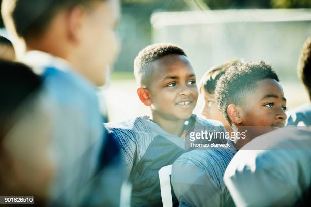 Smiling young football player standing with teammates listening to coach before football game