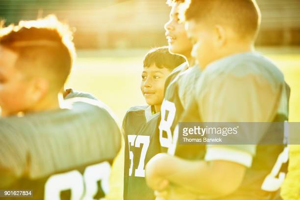 Smiling young football player standing with teammates on field after game