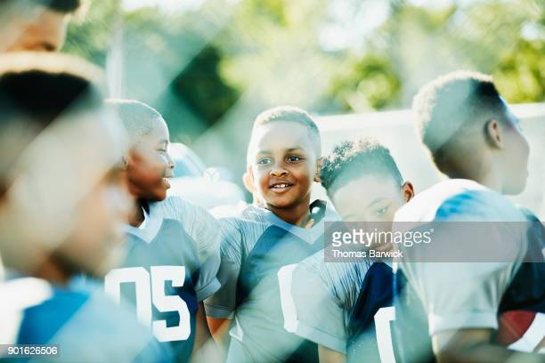 Smiling young football players hanging out together before football game