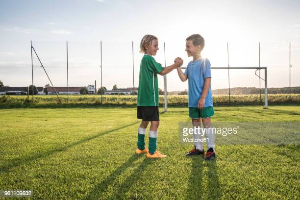 smiling young football players shaking hands on football ground - fair play sport foto e immagini stock