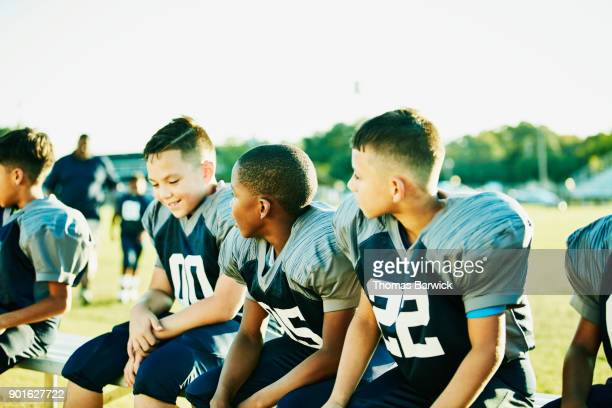 Smiling young football players sitting on bench resting during practice