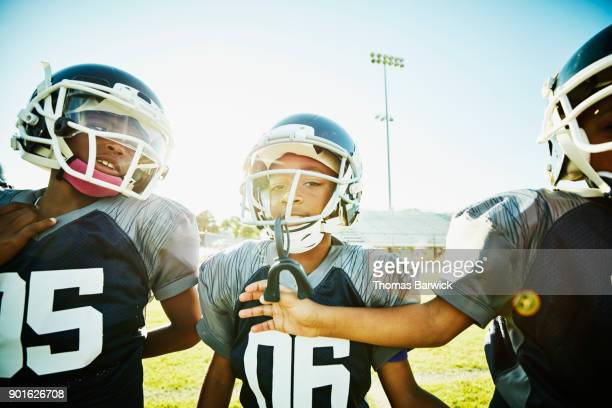 Smiling young football teammates on warming up on field together before football game
