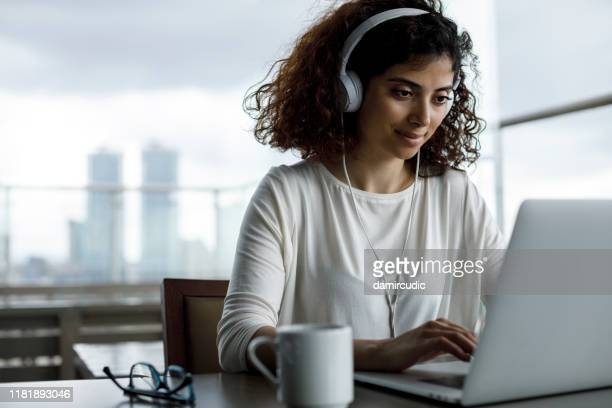 smiling young freelancer girl working at a cafe - surfing the net stock pictures, royalty-free photos & images