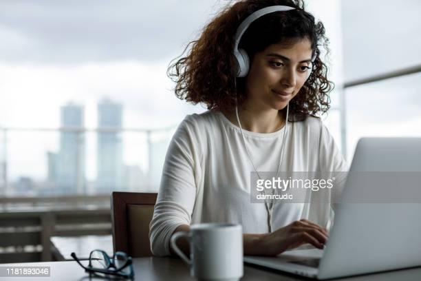 lachende jonge freelancer meisje werkt in een café - midden oosterse etniciteit stockfoto's en -beelden