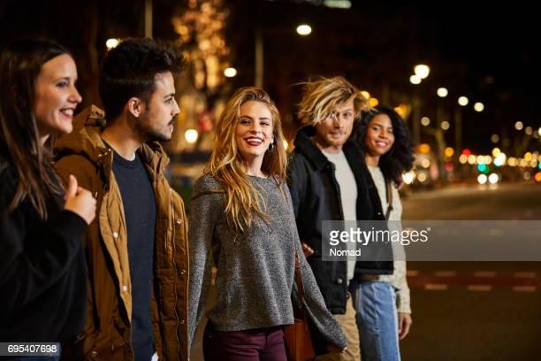 Sonrientes joven amigos cruzar la calle por la noche
