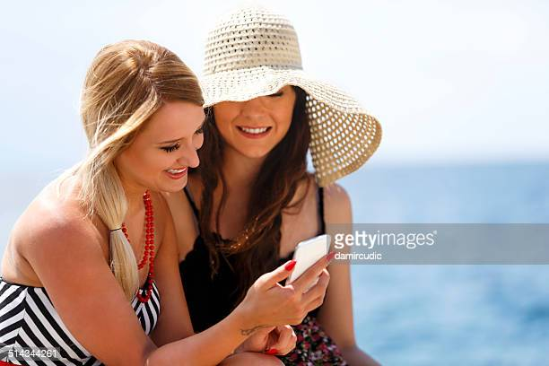 Smiling young friends looking at a mobile phone