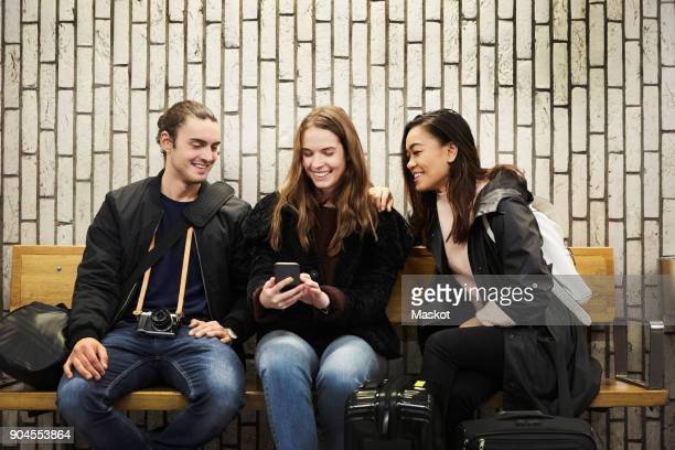 Smiling young friends looking at smart phone while sitting against wall on subway station platform