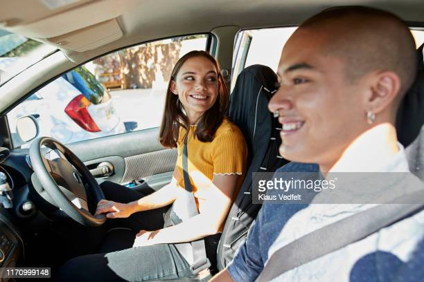 smiling young friends sitting in car on sunny day - part of a series stockfoto's en -beelden