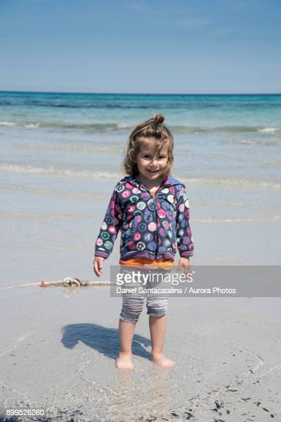 Smiling young girl at Cala Brandinchi beach, San Teodoro, Sardinia, Italy