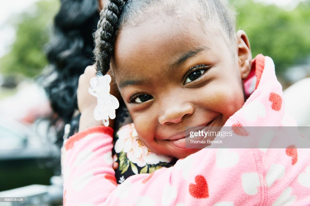Smiling young girl being held by mother : Stock Photo