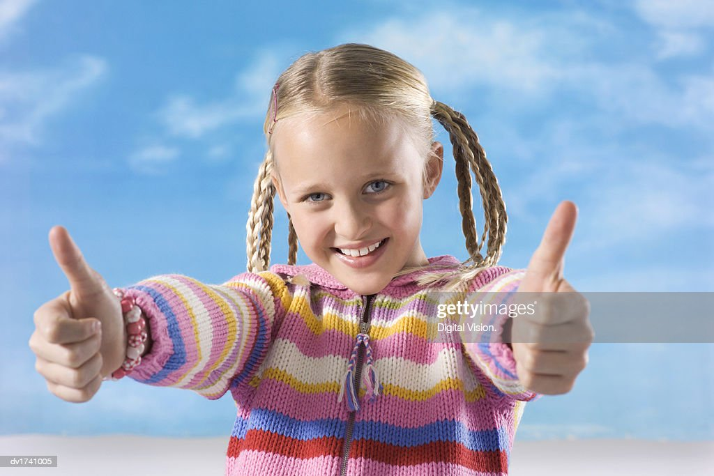 Smiling Young Girl Giving the Thumbs-Up : Stock Photo