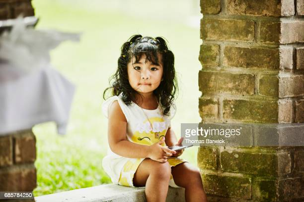 Smiling young girl holding smartphone during backyard birthday party