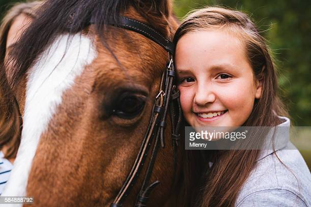 Smiling young girl hugging her horse