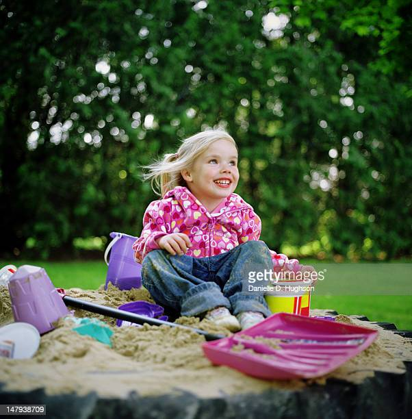 Smiling young girl in sandbox