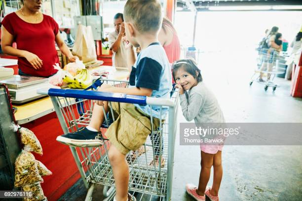 Smiling young girl leaning on shopping cart as mother checks out form produce market