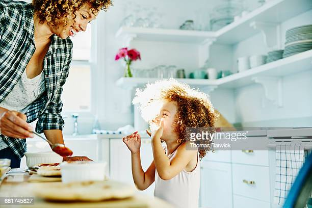 Smiling young girl making pizza with mother