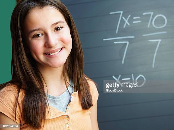Smiling young girl near math problem against the blackboard