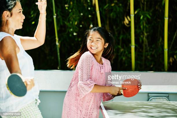 smiling young girl playing table tennis with aunt outdoors on sunny afternoon - aunt stock pictures, royalty-free photos & images