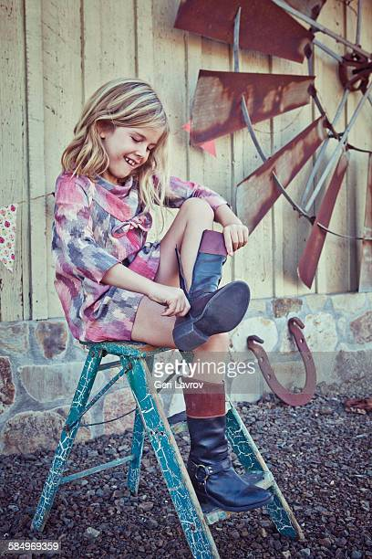 Smiling young girl putting on a boot