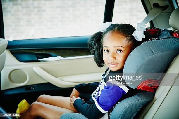Smiling young girl riding in car seat in car