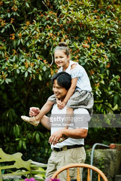 Smiling young girl riding on uncles shoulders in backyard garden