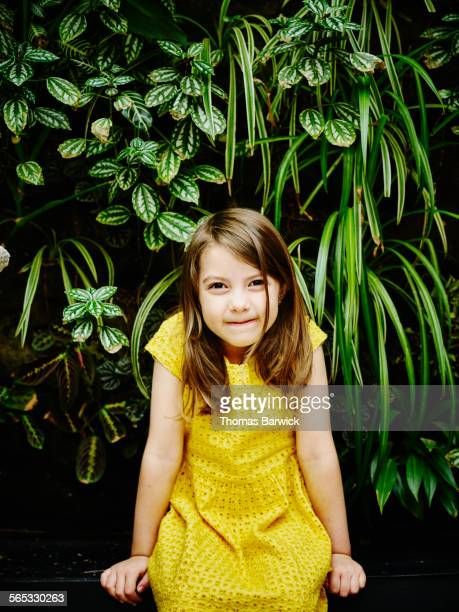 smiling young girl sitting in front of living wall - yellow dress stock pictures, royalty-free photos & images
