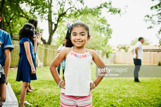 Smiling young girl standing in backyard during family birthday party