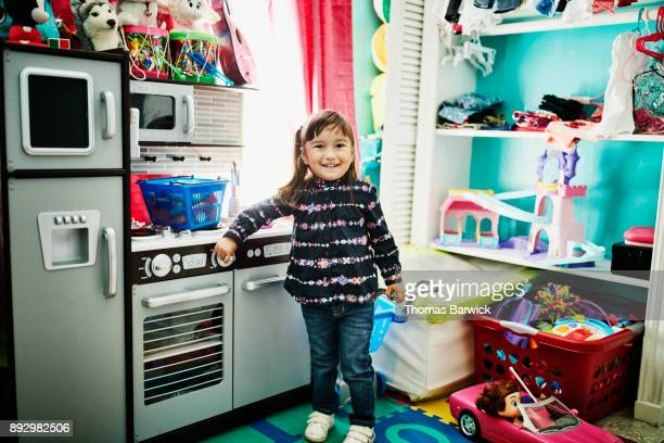 Smiling young girl standing in front of toy kitchen in playroom